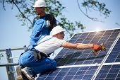 Two workers mounting heavy solar photo voltaic panel on tall steel platform using screwdriver on blue sky background. Exterior stand-alone solar panel system installation, dangerous job concept. poster
