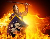 Medieval knight in attack position on fire background. poster