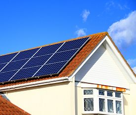 Solar Panels On House Roof Top With Blue Sky Generating Heat Electrical Power For The Customer No Pe
