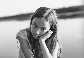 Black And White Portrait Of Sad Beautiful Teen Girl Looking With Serious Face At Seaside During Suns