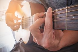 Young Man's Hands Playing Acoustic Guitar.the Guitar Is A Fretted Musical Instrument That Usually Ha