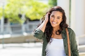 Happy young beautiful woman walking on the street. Portrait of cheerful university student looking at camera while adjusting curly hair with copy space. Latin stylish girl smiling while standing.