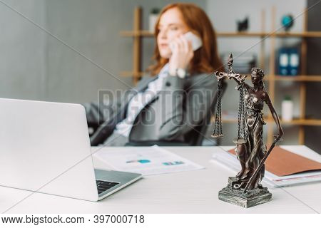Figurine On Table Near Laptop With Blurred Female Lawyer Talking On Phone On Background