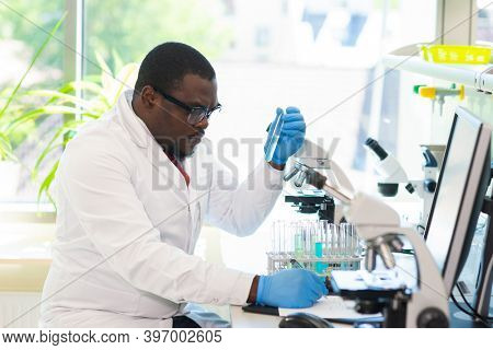 African-american medical doctor working in research lab. Science assistant making pharmaceutical experiments. Chemistry, medicine, biochemistry, biotechnology and healthcare concept.