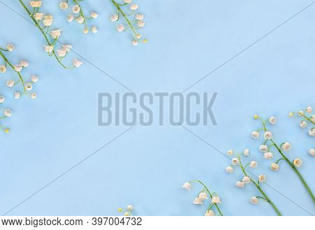 Frame Of White Flowers Lily Of The Valley ( Convallaria Majalis, May Bells, May Lily ) On A Blue Pap