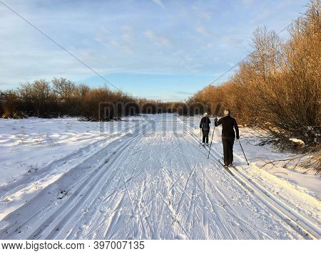 A Couple Cross Country Skiing Along Tracks Using The Classic Method On A Beautiful Sunny Winter Day