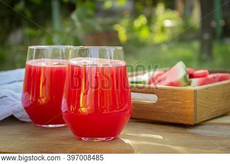 Two Glasses With Fresh Watermelon Juice On A Table In The Garden. Wooden Tray With Watermelon Slises
