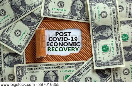 Post Covid-19 Recovery. The Words 'post Covid-19 Economic Recovery' Appearing Behind Torn Brown Pape