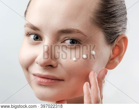 Beautiful Young Woman With Clean Fresh Skin. Drops Of Cream Are Applied On The Cheek. Hand Near The