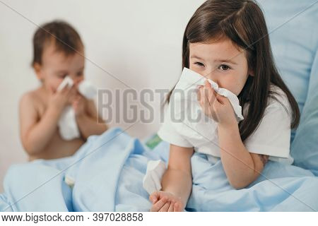 The Little Girl Caught A Cold. Children Sneeze Into A Handkerchief. The Child Is Ill And Is Being Tr
