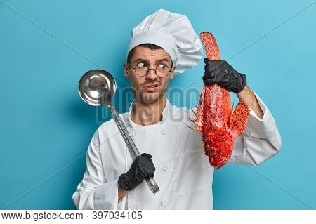 Displeased Male Chef Holds Red Sea Bass And Ladle Prepares Delicious Meal For Restaurant Visitors We