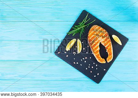 Grilled Salmon Fish On Stone Board. Salt Atlantic Salmon Fried On Grill With Lemon. Top View