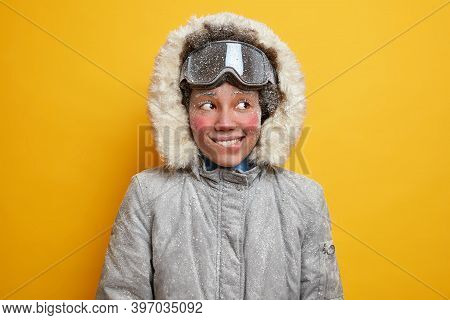 Portrait Of Cheerful Frozen Woman Bites Lips And Looks Away Gladfully Has Adventure Or Winter Expedi
