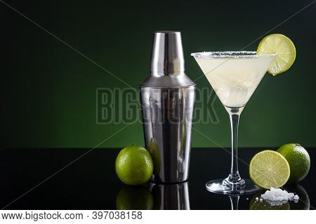 Typical Mexican Margarita Cocktail With Lime Slice Ice And Cocktail Shaker On  Black And Green Backg