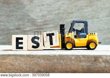 Toy Forklift Hold Letter Block T To Complete Word Est (abbreviation Of Established, Estimated, Easte