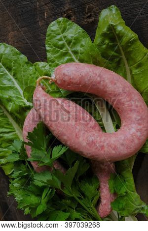Sausage Ring, Garlic, Chard And Parsley Sprigs,red Chili On Brown Wooden Board On Wooden Table Backg