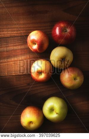 High angle still life of a group of  fresh picked apples on a rustic wood table. Fuji, Gala, Granny Smith, Braeburn, Golden Delicious with warm side light.