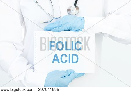 Doctor Holds A Card With The Name Of The Diagnosis Folic Acid. Medical Concept.