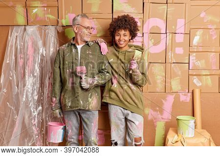 Happy Diverse Couple Renovate Their Apartment Pose With Painting Tools Wears Dirty Clothes After Ref