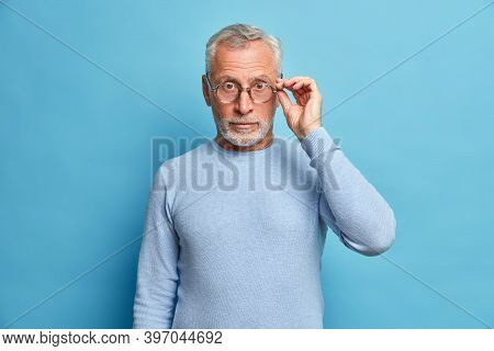 Studio Shot Of Surprised Mature Man Looks With Wonder Wears Optical Glasses And Casual Jumper Hears