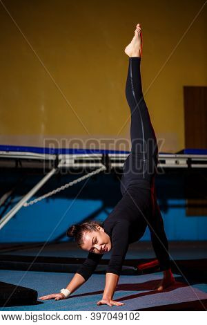 Young Sportive Girl Doing Handstand Exercise. Young Woman Doing Twine While Standing On Hands