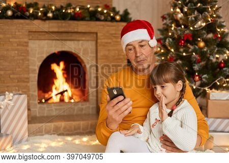 Shot Of Happy Little Girl And Her Grandparents Sitting On Floor On Soft Carpet During Christmas Morn