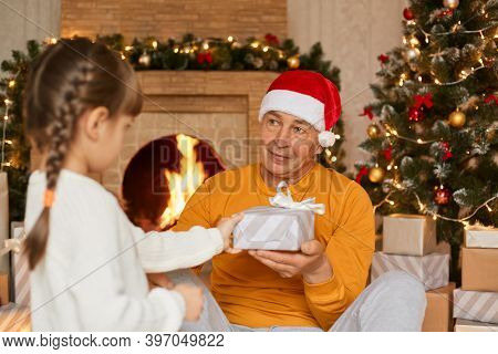Grandfather With Granddaughter Giving Present On Christmas, Child With Pigtails In White Jumper Cong
