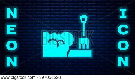 Glowing Neon Shovel In Snowdrift Icon Isolated On Brick Wall Background. Vector