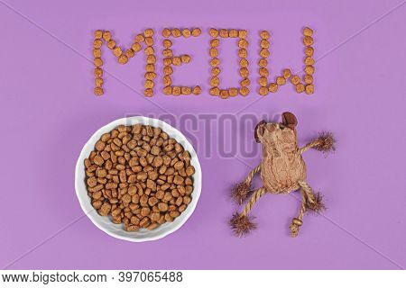 Bowl With Dry Cat Food And Kibbles Forming Word 'meow' And Cat Toy Mouse On Purple Background