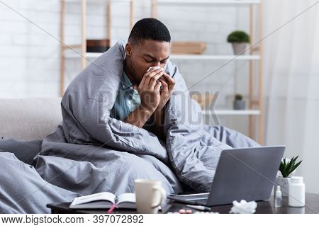 Ill African Man Having Rhinitis Sneezing And Blowing Runny Nose In Paper Tissue Sitting On Sofa At H