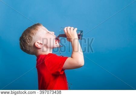 A Blond European Boy Of 6 Years Old Drinks Juice From A Glass. A Child In A Red T-shirt Splashes And