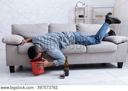 Alcohol Poisoning. Drunk Man Vomiting Into A Bucket After Drinking Alcoholic Wine Lying On Sofa At H