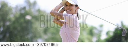Female Golfer Smiles And Looks Along After Making Hit With Club. Womens Golf Concept