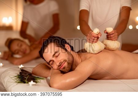 Spouses Enjoying Herbal Back Massage And Aromatherapy Lying And Relaxing In Spa Center Indoors. Mass
