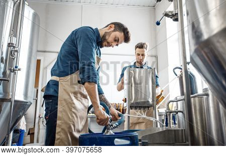 Plant Workers Operate Equipment On Productions Of Craft Drink And Modern Plant. Busy Young Attractiv