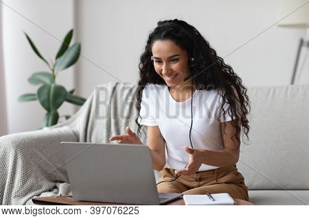 Joyful Young Woman With Headset Having Online Conference, Working From Home, Copy Space. Happy Curly