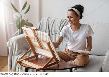 Happy Woman With Easel And Palette Painting At Home, Copy Space. Portrait Of Young Lady Painting For