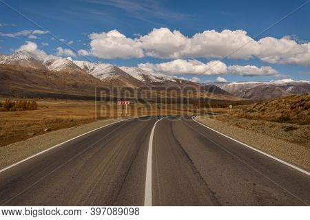 Colorful Autumn Landscape With A Winding Asphalt Road In The Steppe And Mountains Covered With Snow