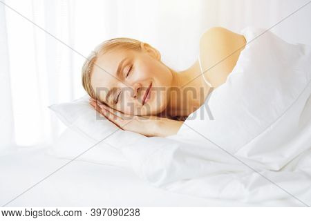 Beautiful Young Woman Sleeping In Sunny Bedroom Comfortably And Blissfully. Waking Up In Fairy Morni