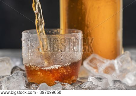 Whiskey Or Bourbon In A Frosted Glass With Ice. Alcoholic Beverage