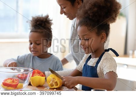 Smiling Black Foster Mother Watching Adopted Children Cooking Vegetable Dish