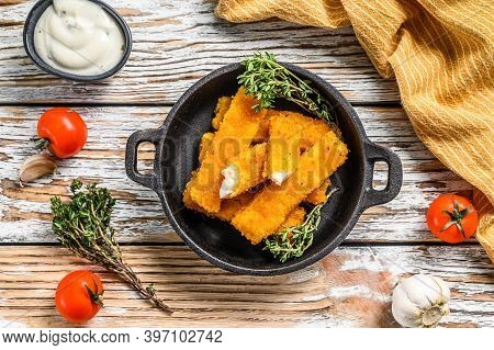 Crispy Fish Fingers With Breadcrumbs Served With Sauce Tartar In A Pan. White Background. Top View
