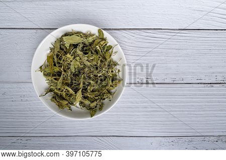 Pile Of Dried Stevia Rebaudiana Bertoni In Plate On White Wood Background. Natural Sweetener From St
