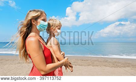 Mother Put Medical Mask On Child On Sea Beach. New Rules To Wear Cloth Face Covering At Public Place