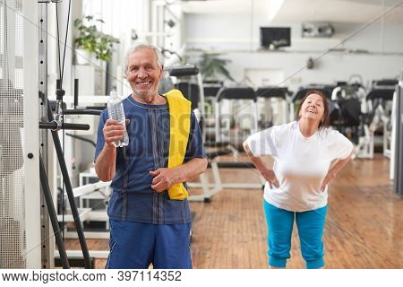 Happy Senior Man With Bottle Of Water At Gym. Smiling Elderly Man Drinking Water After Gym Session.