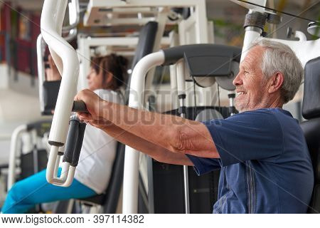 Senior Man Training At Gym, Side View. Elderly Caucasian Man Training On Machine At Fitness Club. Tr