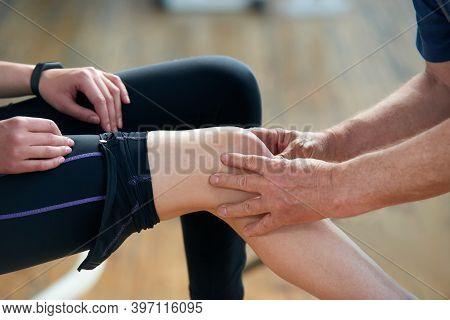 Girl Injured Her Leg During Gym Training. Older Therapist Examining Female Injured Knee At Fitness C