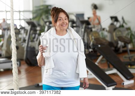 Senior Woman Holding Bottle Of Water At Gym. Happy Elderly Woman Looking At Camera At Sport Club. Pe