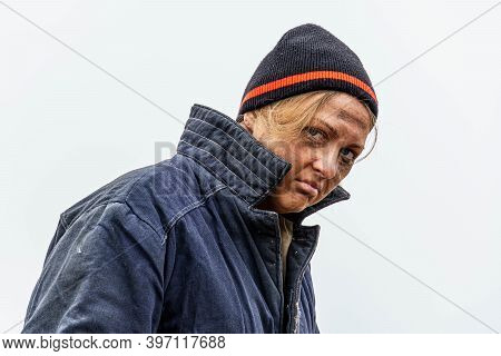 Dirty, Sad Homeless Woman 30-40 Years Old, Against A Gray Sky. Homeless Poor Life Concept. Copy Spac