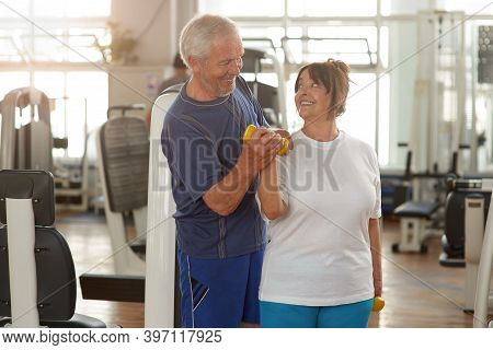 Happy Couple Of Seniors Training At Gym Together. Smiling Elderly Couple Looking At Each Other Durin